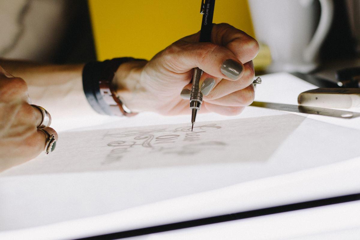 person illustrating in design studio